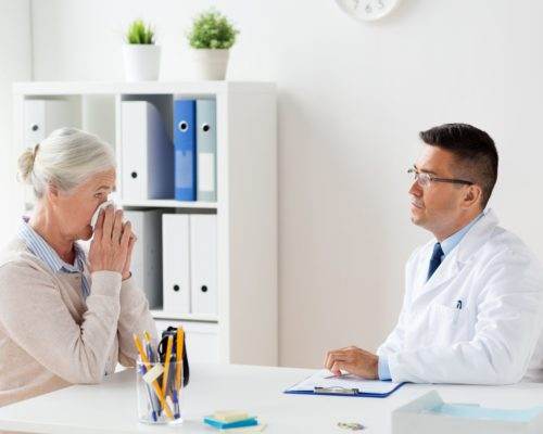 medicine, age, healthcare and people concept - senior woman and doctor with clipboard meeting at hospital